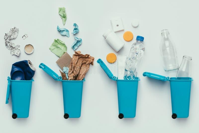 odgórny widok kosz na śmieci i asortowany śmieci odizolowywający na popielatym, przetwarza pojęcie obrazy royalty free