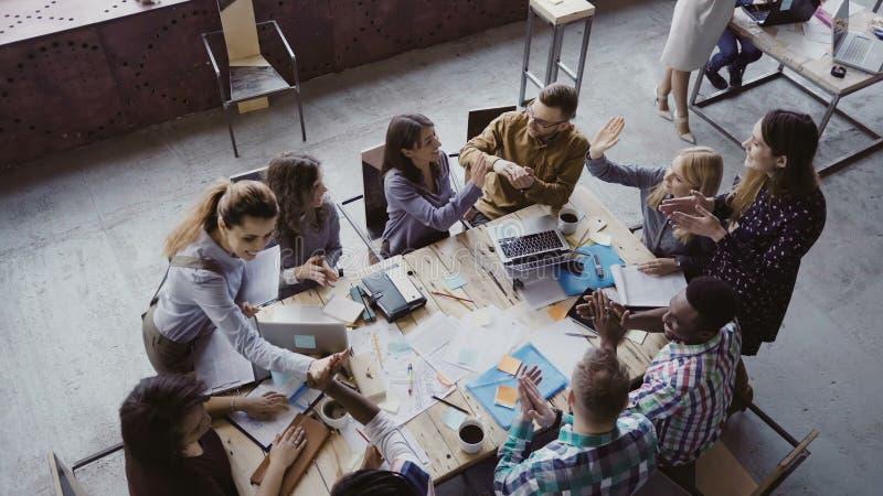 Odgórny widok kreatywnie biznes drużyna pracuje przy nowożytnym biurem Koledzy opowiada, ono uśmiecha się, wysoko pięć z each inn zdjęcie stock
