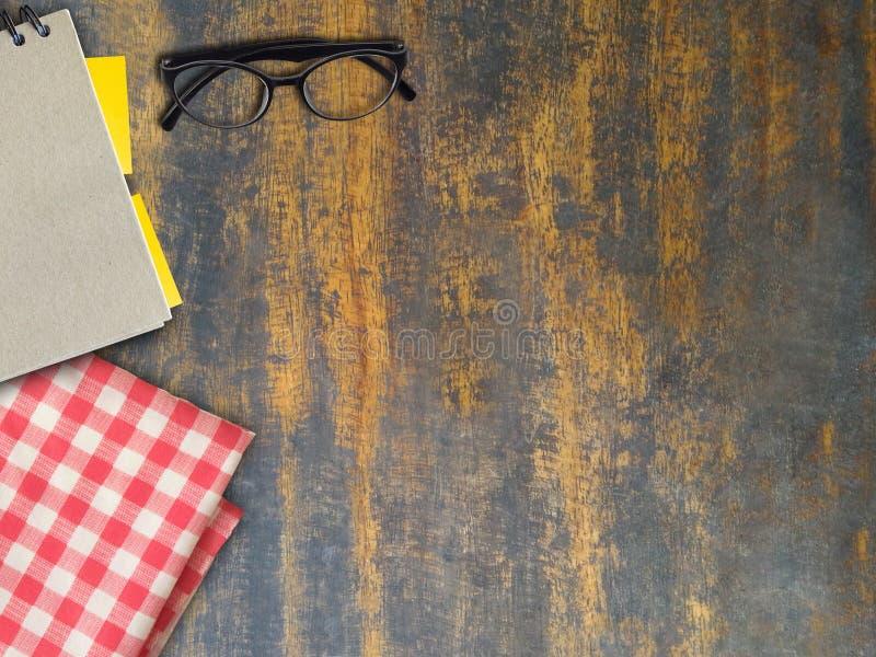 Odgórny widok książka, eyeglasses i szkocka krata na drewnianym brąz, mo zdjęcie royalty free