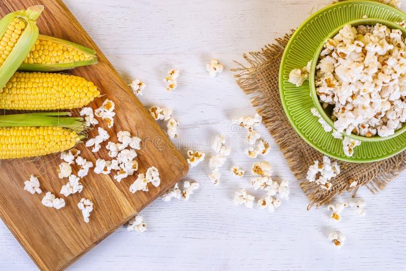 Odgórny widok kukurydzani produkty na białym drewnianym tle Popkorn, kukurudza i kukurydzani pyły, zdjęcia stock