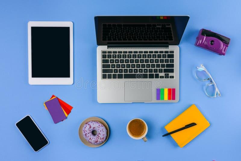 Odgórny widok laptop, cyfrowa pastylka, smartphone, filiżanka kawy z pączkiem i kamera, obrazy stock