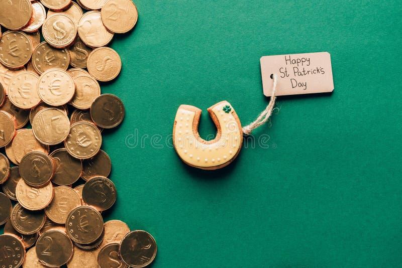 odgórny widok lodowacenia ciastko w kształcie podkowa i złote monety na zieleni, st patricks zdjęcie royalty free