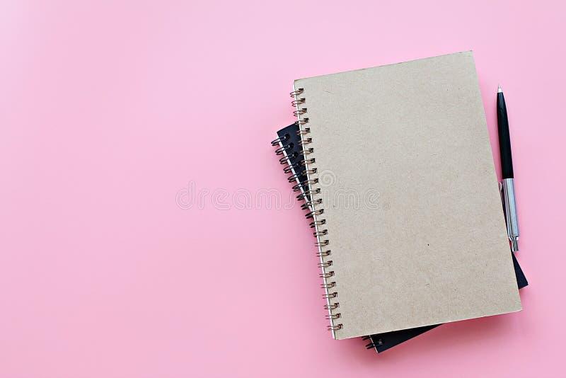 Odgórny widok lub mieszkanie nieatutowi notatniki i pióro na różowym tle fotografia royalty free