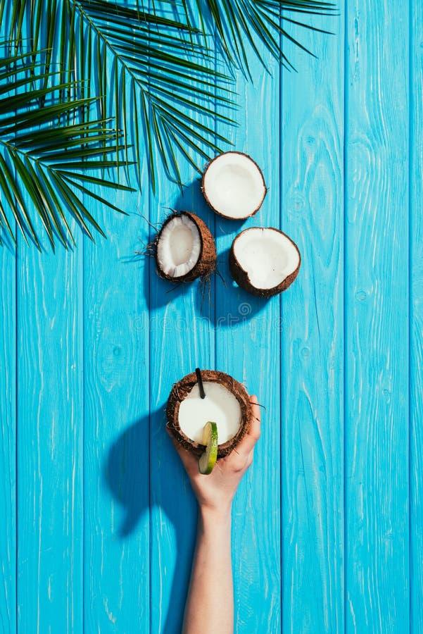 odgórny widok ludzka ręka z kokosowym koktajlem, krakingowymi koks i palmą, opuszcza na turkusie zdjęcie royalty free