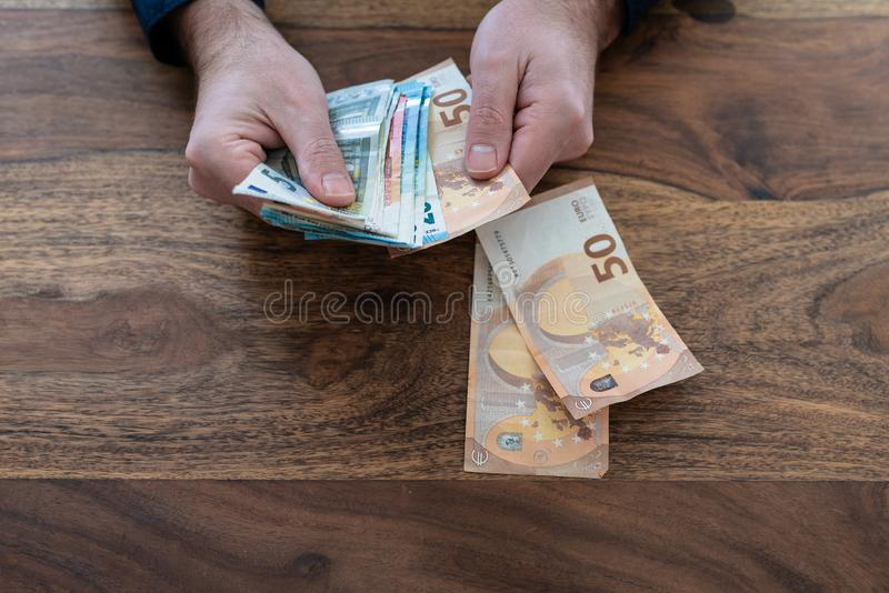Odgórny widok mężczyzny odliczający pieniądze przy biurkiem obraz stock