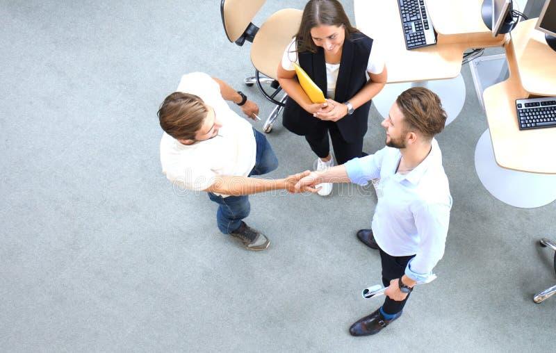 Odgórny widok młodzi partnery biznesowi trząść ręki nad transakcją przy biurem Ostrość na ręki potrząśnięciu zdjęcia royalty free