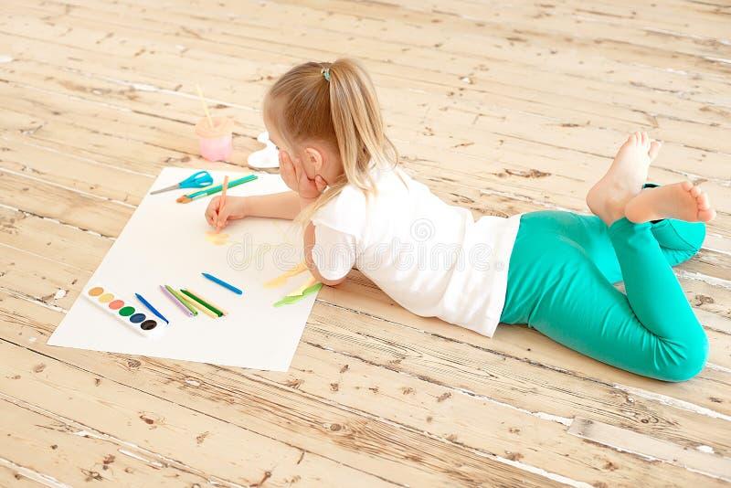 Odgórny widok mały blondynki dziewczyny obraz na dużym białym papierze podczas gdy kłaść na podłoga indoors obrazy royalty free