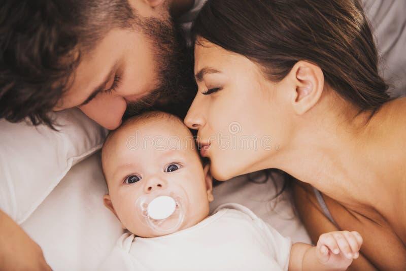 Odgórny widok Matki i ojca buziaków dziecko w łóżku fotografia stock