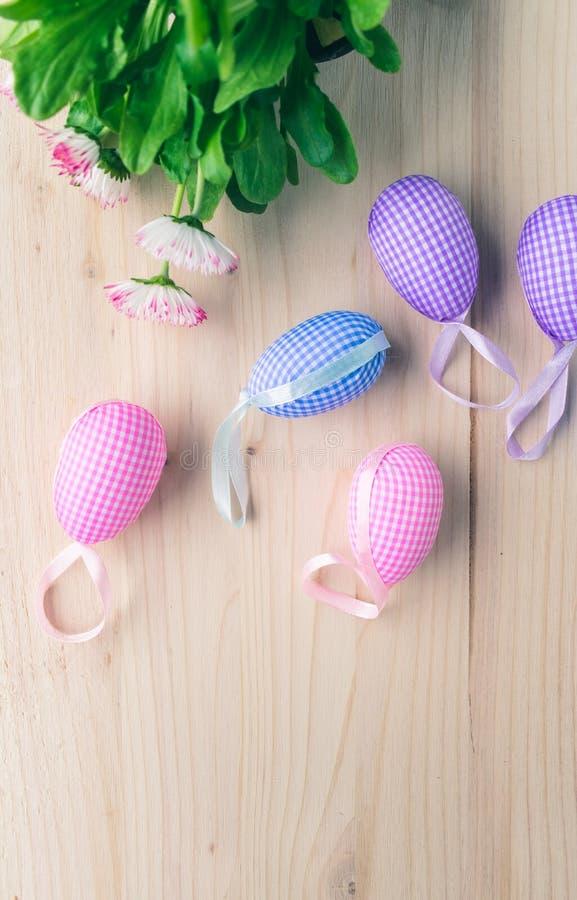 Odgórny widok menchie i błękitne w kratkę Wielkanocne jajko stokrotki na bladym drewnianym tle dekoracji, białych i różowych zdjęcie stock