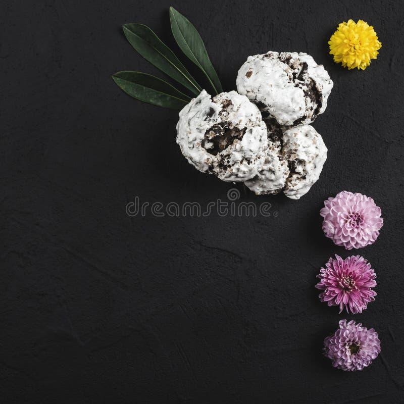Odgórny widok menchie, kolorów żółtych kwiaty i ciastka na czerń kamienia stole, obrazy royalty free