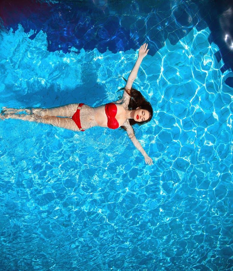 Odgórny widok moda seksowny bikini garbnikował modela w błękitne wody swimm zdjęcia royalty free