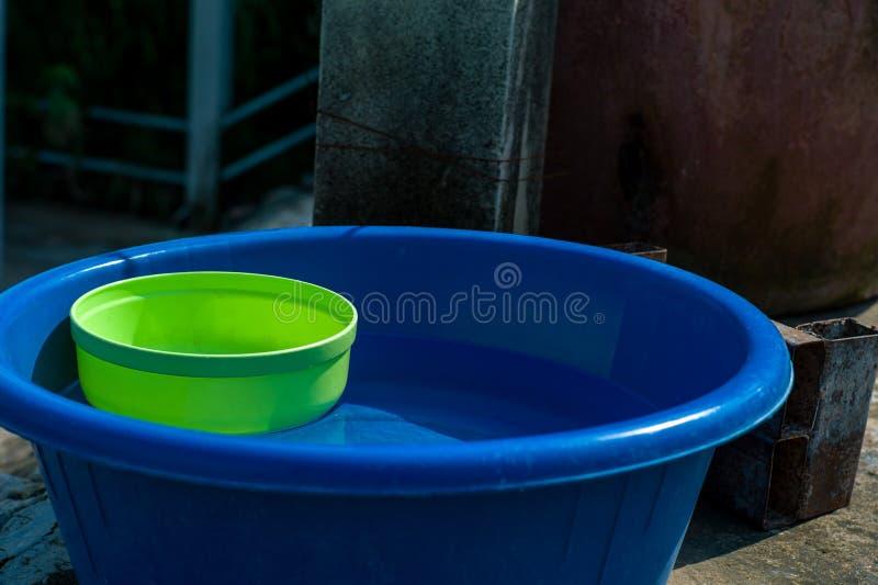Odgórny widok mydło w plastikowym koszu i muśnięciu dla pralni z plastikową butelką stawiającą na betonowej podłodze w pogodnym s obrazy stock