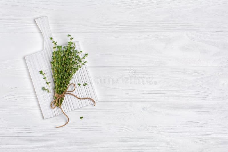 Odgórny widok na świeżym macierzanki zieleni ziele z dratwy arkaną na białej drewnianej desce fotografia stock