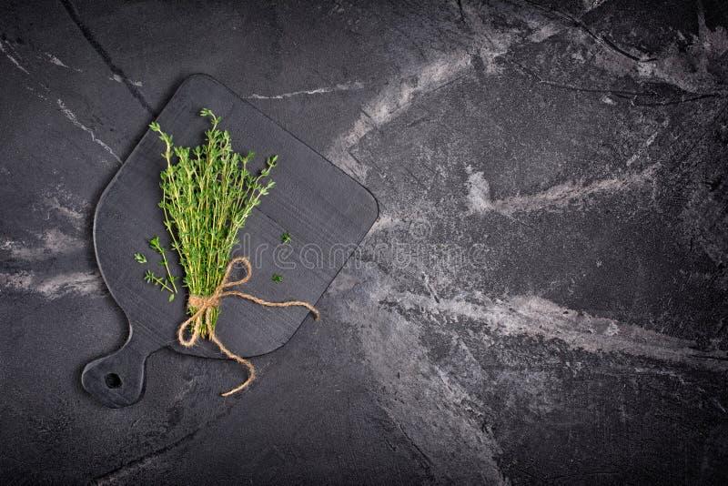 Odgórny widok na świeżym macierzanki zieleni ziele z dratwy arkaną na czarnej drewnianej desce zdjęcie royalty free