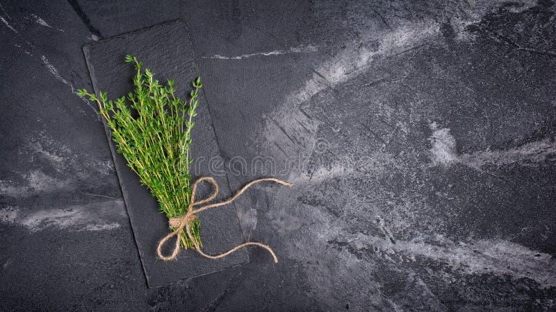 Odgórny widok na świeżym macierzanki zieleni ziele z dratwy arkaną na czerń łupku desce obrazy royalty free