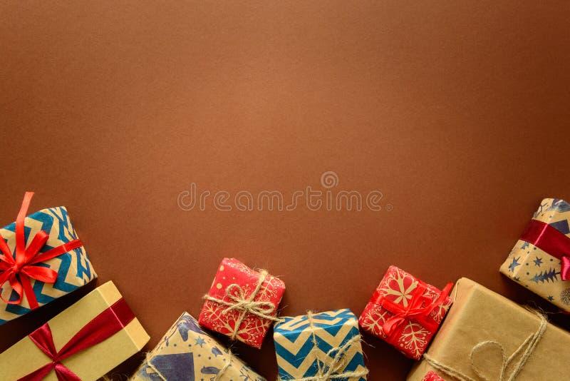 Odgórny widok na Bożenarodzeniowych prezentach zawijających w prezenta papierze dekorował z faborkiem na brown papieru tle zdjęcia royalty free