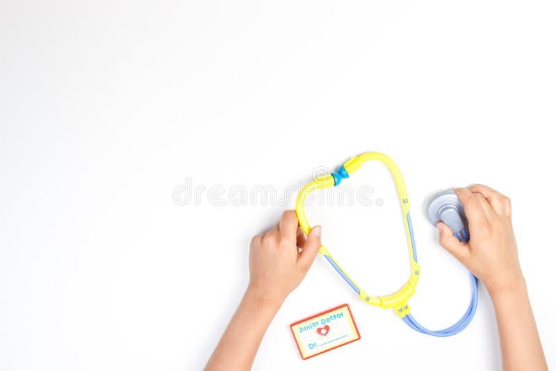 Odgórny widok na dziecka ` s rękach z zabawkarskim stetoskopem na białym tle zdjęcia royalty free