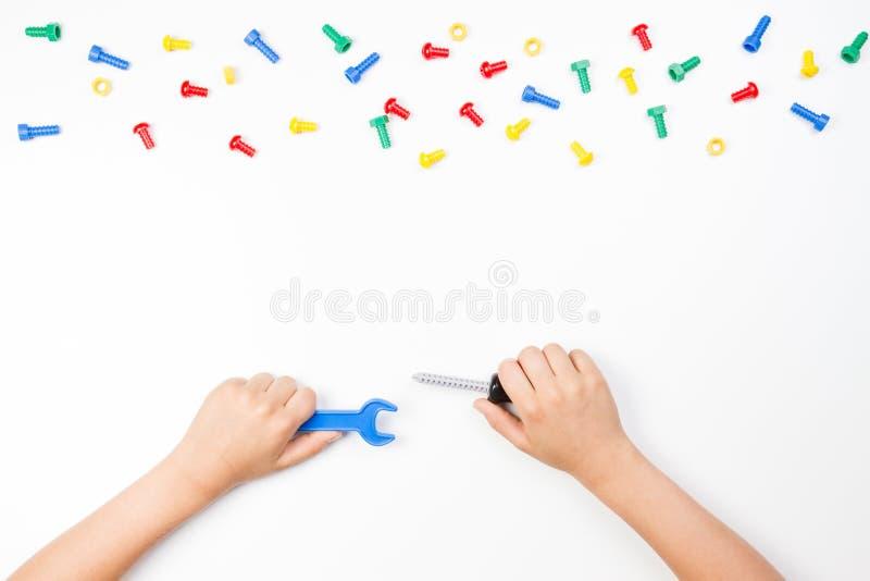 Odgórny widok na dziecka ` s wręcza bawić się z kolorowymi zabawek narzędziami na białym tle zdjęcia royalty free