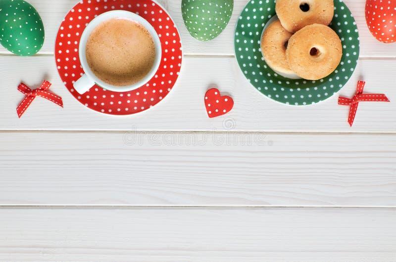 Odgórny widok na kawy espresso filiżance, talerzu ciastka i Wielkanocnych jajkach na l, obraz stock