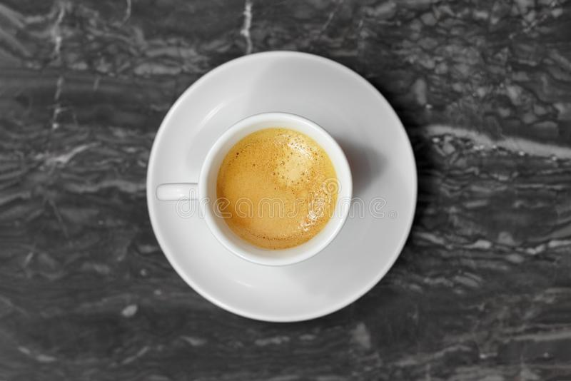Odgórny widok na małej filiżance i spodeczku, z kawową kawą espresso na czarny i biały marmurowym tle, zdjęcie stock