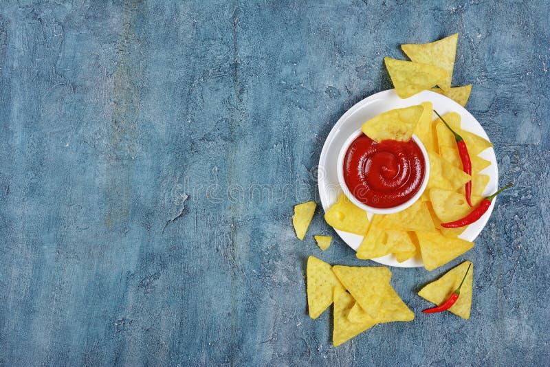 Odgórny widok na meksykańskich nachos szczerbi się z korzennym czerwonym kumberlandem lub upadem w białym pucharze i gorący chili zdjęcia stock