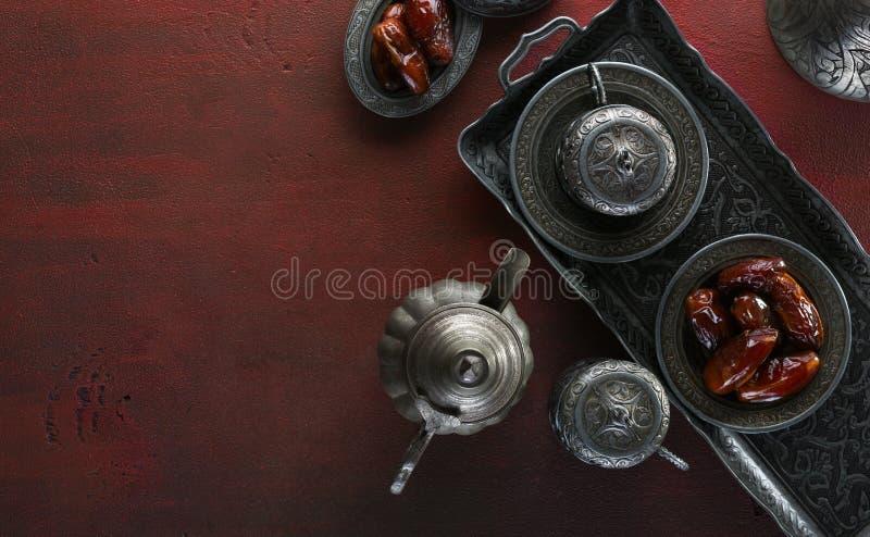 Odgórny widok na srebnym talerzu z daktylowymi owoc i filiżankami na zmroku - czerwony drewniany tło t?o ramadan kareem Ramadan zdjęcie royalty free