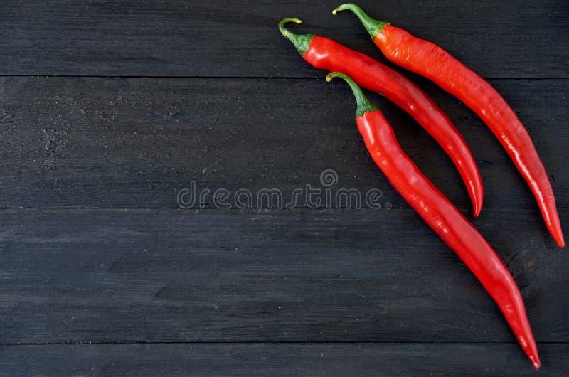 Odgórny widok na trzy gorących chili pieprzach nad czarnym drewnianym tłem z kopii przestrzenią widok ogólny zdjęcia stock