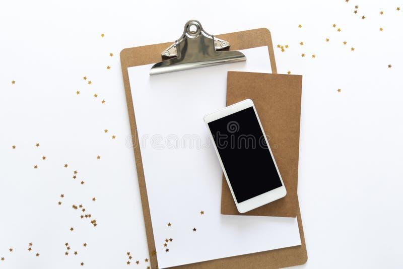 Odgórny widok nad pracującym biurkiem z papierem, notatnikiem i telefonem przy wierzchołkiem z przypadkowo opuszczać złotymi gwia fotografia stock