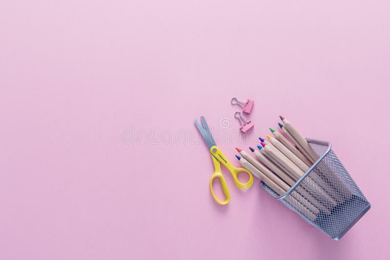 Odgórny widok nad różowym tłem z szkolnymi dostawami na nim Coloured ołówki, papierowe klamerki i nożyce jak z powrotem szkoła, zdjęcia royalty free