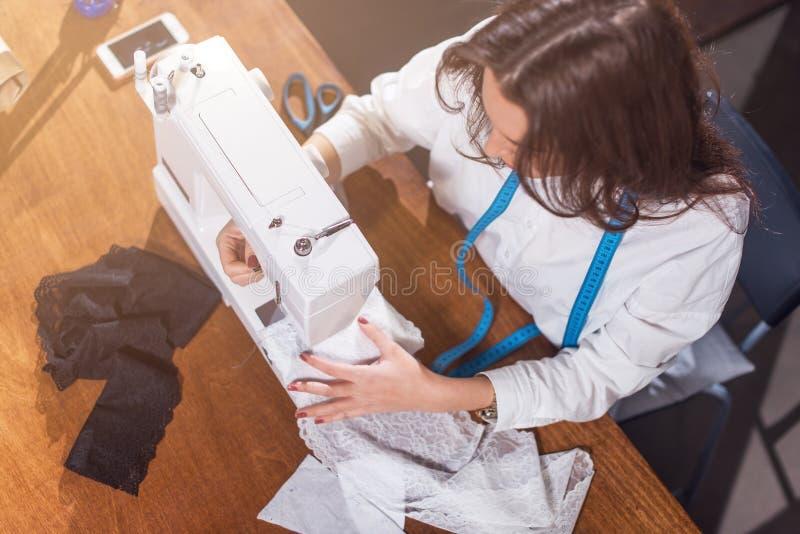 Odgórny widok needlewoman zaszywania tkanina na szwalnej maszynie przy miejscem pracy w studiu zdjęcie royalty free