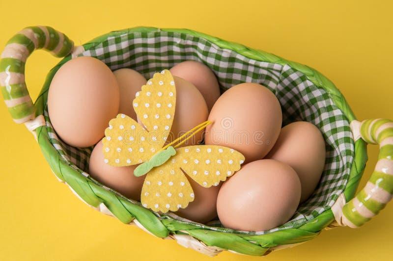 Odgórny widok Nieociosani brązów jajka w łozinowym koszu wykładali z w kratkę tkaniną Wystrój odczuwany motyl Żółty tło zdjęcia stock