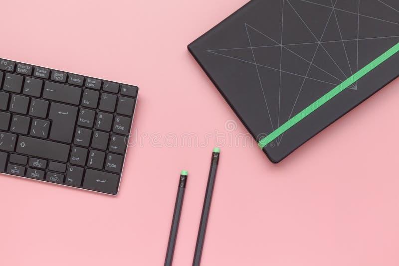 Odgórny widok, notatnik i ołówek z klawiaturą na różowym tle, mieszkanie nieatutowy styl obrazy stock