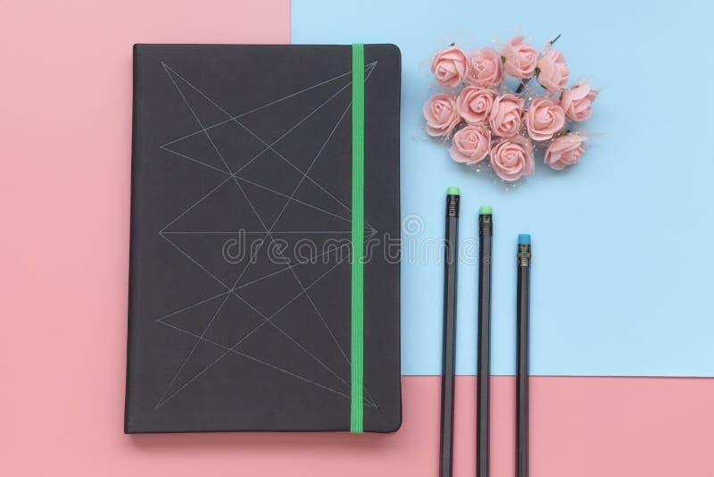 Odgórny widok, notatnik z kwiatami i ołówki na tle, różowym i błękitnym mieszkanie nieatutowy styl zdjęcia stock