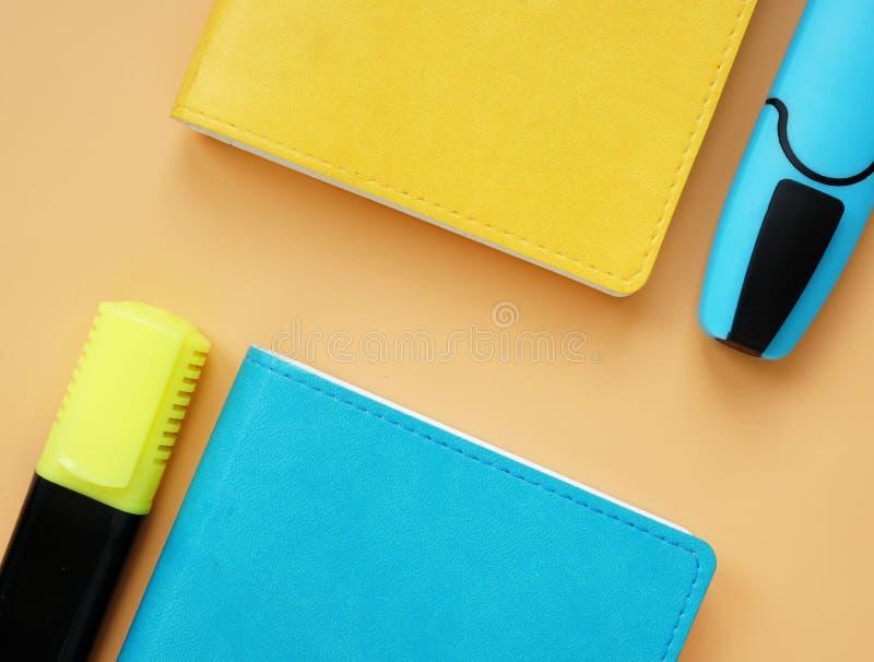 Odgórny widok notepads i markiery na pomarańczowym biurku błękitni i żółci zdjęcia stock