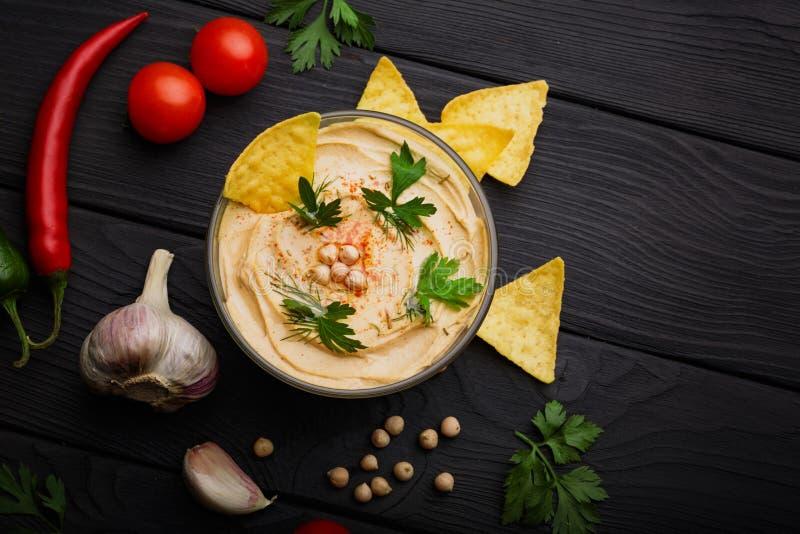 Odgórny widok odżywczy hummus w szklanym pucharze i warzywach Arabski naczynie z nachos na czarnym drewnianym tle zdjęcie royalty free