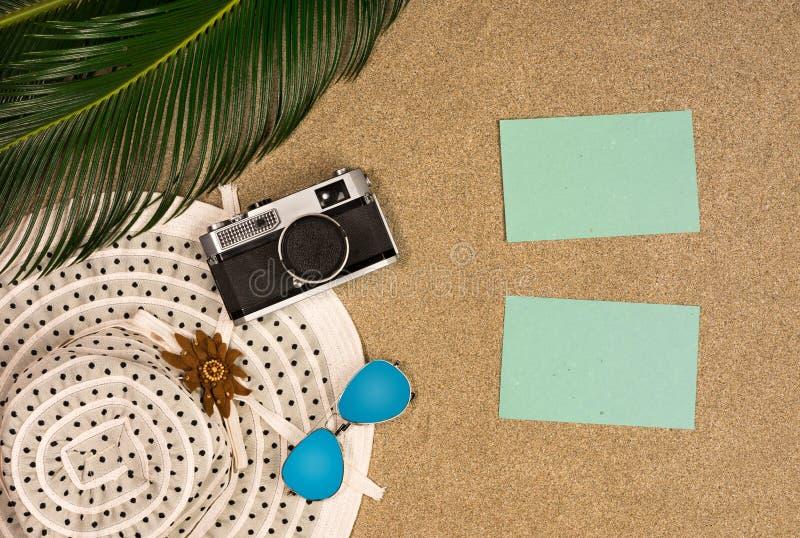Odgórny widok palma liście, retro fotografii kamera i okulary przeciwsłoneczni na plażowym piaska tle, Mieszkanie nieatutowy samo obrazy stock
