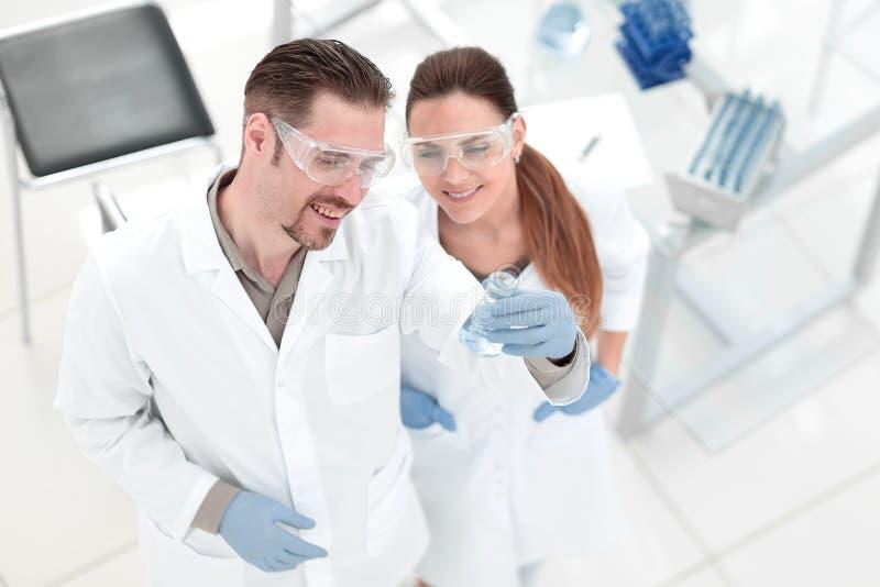Odgórny widok para technicy patrzeje tubki z cieczem fotografia stock