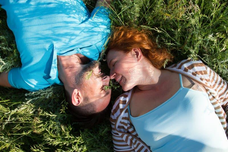 Odgórny widok para z zamkniętymi oczami w miłości kłama na zielonej trawie twarz w twarz i nosie ostrożnie wprowadzać obraz royalty free