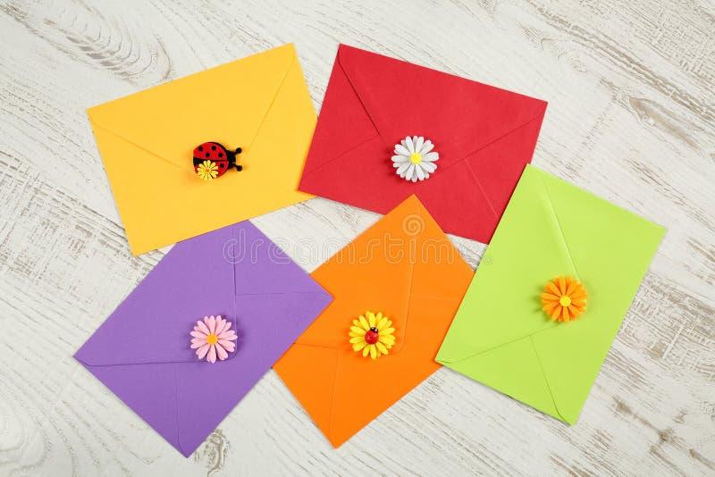 Odgórny widok pięć kolorowych kopert od przetwarzającego papieru z dekoracyjnymi kwiatów płatkami, biedronkami na białym drewnian fotografia stock
