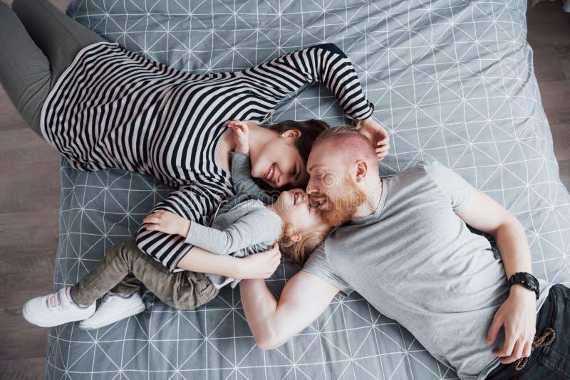 Odgórny widok piękni potomstwa matkuje, ojciec, ich córka i podczas gdy kłamający na łóżko głowie patrzeje kamerę i ono uśmiecha  zdjęcia stock