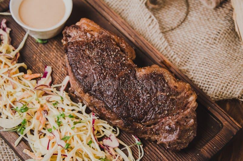 Odgórny widok piec na grillu ribeye wołowiny stek z gulasz kapustą i wineglass dalej czerwone wino, ziele i pikantność nad brown  zdjęcie royalty free