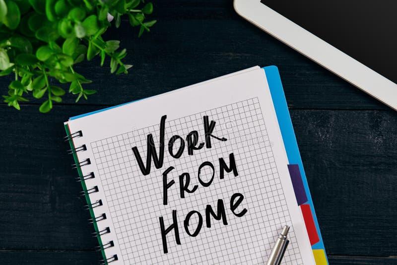 Odgórny widok pisać z pracą OD DOMOWEJ inskrypci otwarty notatnik Zielony kwiat, pastylka, pióro i notatnik na drewnianym, zdjęcie royalty free