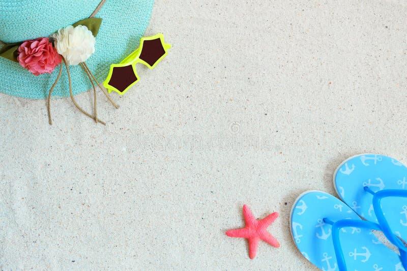 Odgórny widok plażowy piasek z słomianym kapeluszem, okularami przeciwsłonecznymi, kapciami i rozgwiazdą, fotografia royalty free