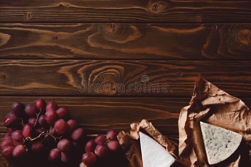 odgórny widok plasterki ser na zmiętym papierze i dojrzałych czerwonych winogronach zdjęcia stock