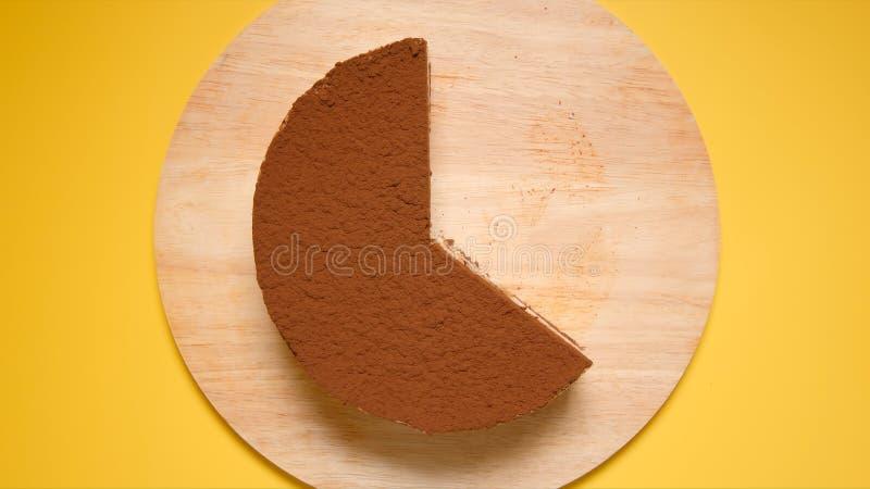 ODGÓRNY widok: Połówka Czekoladowy tort na żółtym tle fotografia stock