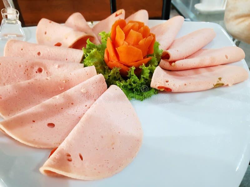 Odgórny widok pokrajać wieprzowina baleron lub bologna z sałatą i marchewką na bielu talerzu fotografia royalty free