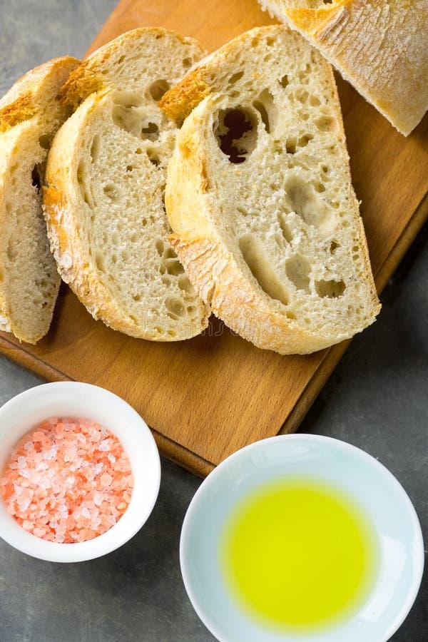 Odgórny widok Pokrojonego rzemieślnika Nieociosany chleb na Drewnianej Tnącej desce z solą i oliwa z oliwek na zmroku betonu stol zdjęcie royalty free