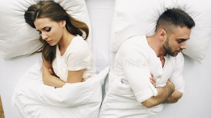 Odgórny widok potomstwa spęczenia pary lying on the beach w łóżku problemy po bełta i gniewnego each inny w domu obrazy royalty free