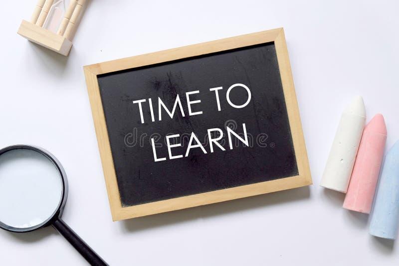Odgórny widok powiększać - szkła, hourglass, kreda i blackboard pisać z &-x27; CZAS LEARN&-x27; na białym tle zdjęcia royalty free