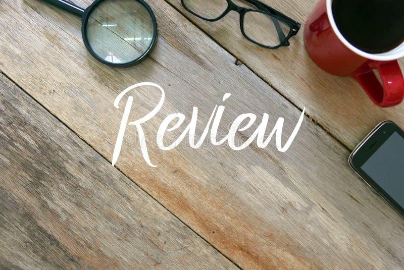 Odgórny widok powiększać - szkło, sunglases, filiżanka kawy i telefon komórkowy na drewnianym tle pisać z przeglądem, obraz royalty free